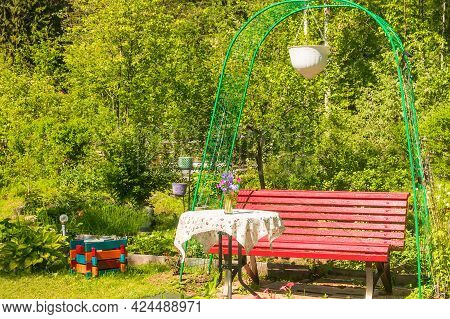 A Small Part Of The Garden Area With A Seating Area. A Comfortable Wooden Bench With A Table And Tab