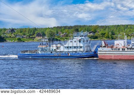 View Of A Tugboat Pushing A Heavy Barge Down The River Along The Shore. River Transportation Of Good