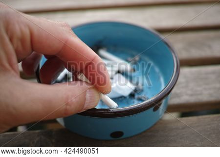 Macro Shot Of A Hand Putting Up A Cigarette Butt On The Ashtray