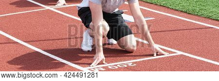A High School Boy Is On His Mark At The 200 Meter Start Line On A Red Track During Track And Field P