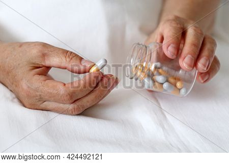 Elderly Woman With Pills In Wrinkled Hands. Medication In Capsules, Taking Sedatives, Antibiotics Or