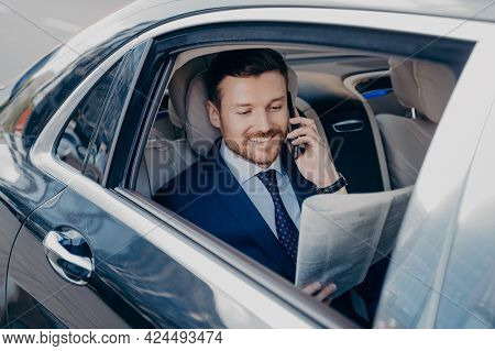 Elegant Businessman In Formal Stylish Wear Traveling In Luxury Car, Reading Newspaper And Searching