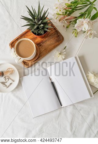 Opened Book, Coffee And Flowers Top View On White Bed. Mock Up Design