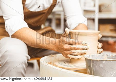 A Young Male Potter Works In His Workshop On A Potters Wheel And Makes Clay Products. Close-up Of Ha