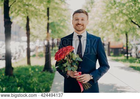 Happy Young Man With Neat Beard In Elegant Formal Dark Blue Suit Walking Joyfully Along Green Alley