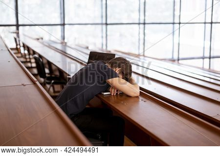 A Male Caucasian Person Sitting And Feeling Tired In The Lecture Hall Auditorium, Overworking Stress