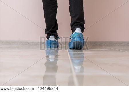A Hospital Patient Visitor Walking In The Shoe Covers To Protect Hygiene On The Floor
