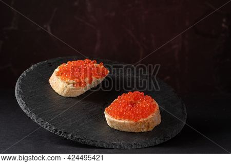 Sandwiches With Red Caviar On A Black Tray. Serving Caviar Sandwiches. Red And Black. Front View.