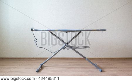 The Empty Simple Iron Board At Home Against The Wall, Chore Laundry Household Concept