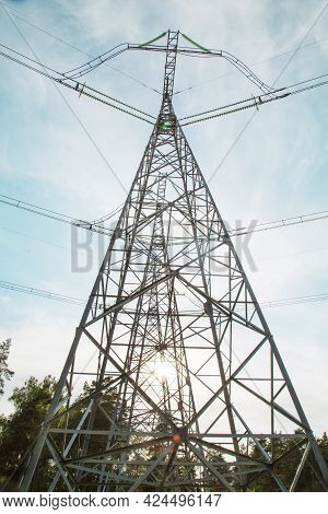 View Of The Masts Of The Power Line Against The Background Of Blue Sky, White Clouds, Beautiful Gree
