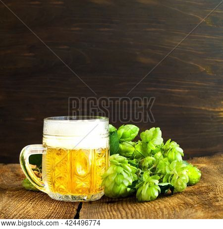 Fresh Hops And Glass Mug With Light Beer On Wooden Background. International Beer Day Or Oktoberfest
