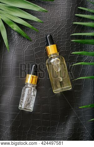 Collagen Serum Or Hyaluronic Serum In Dropper On Black Color Crocodile Skin Texture Background With