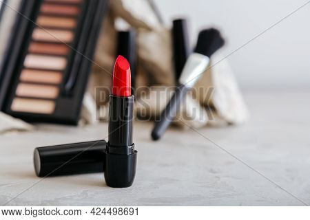 Red Scarlet Lipstick And Set Of Decorative Cosmetics For Make Up On Gray Concrete Background With Co