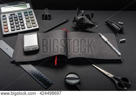 Black Magazine On A Black Table. Accounts Department And Office. Smartphone And Calculator On The Ta