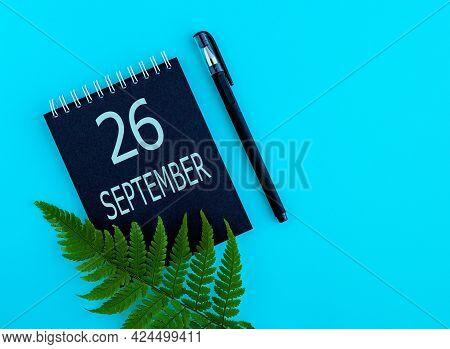 September 26th. Day 26 Of Month, Calendar Date. Black Notepad Sheet, Pen, Fern Twig, On A Blue Backg