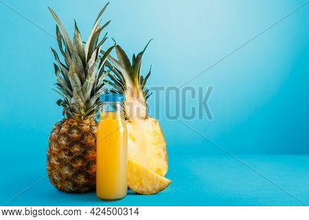 Tasty Pineapple Juice In Glass Bottle With Ingredients On Blue Color Summer Background With Copy Spa