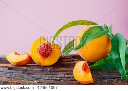 Peaches With Leaves On Wooden Board. Peach In Halves With Bone, Chopped Pieces Wedges Peach Halves.