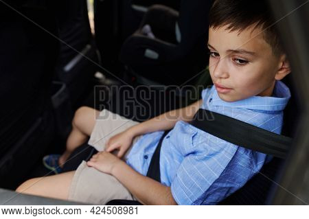 A Teenage Boy Wearing Seat Belts Travels By Car In A Protective Child Booster Car Seat. Traveling Sa