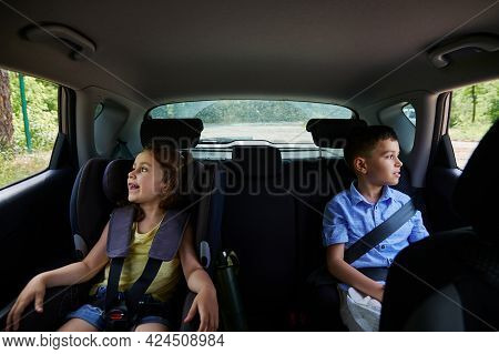 Buckled Two Children Passengers , Boy And Girl, Traveling In A Safety Booster Seat Inside The Car. S