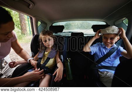 Mother Fastening Her Cute Daughter To Child Safety Seat Inside Car. Children On Safety Booster Car S