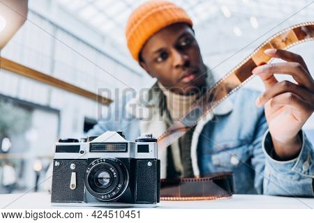 Concentrated African-american Man Photographer In Denim Jacket Checks Vintage Film At Table Focus On