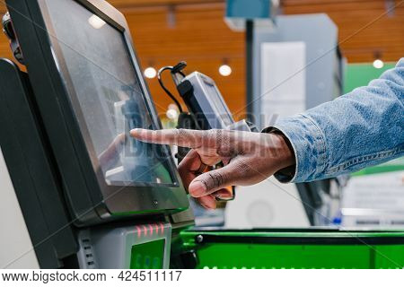 African-american Man Finger Touches Screen Of Self-pay Point To Pay In Shopping Mall Supermarket Lig