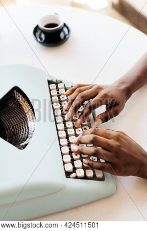 Hands typing on retro light blue pastel typewriter