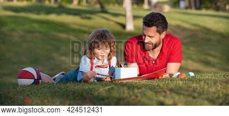 Father And Son Relax On Grass In Park Learning To Draw, Fatherhood