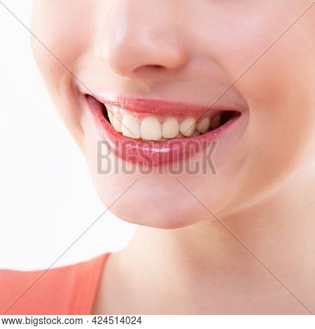 Laughing woman, female mouth with great teeth over white background. Healthy beautiful smile. Teeth health, whitening, prosthetics and care. Happiness and joy concept
