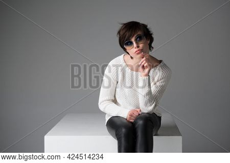 Excited young woman with sunglasses sitting on white cube in studio isolated over gray background, looking at camera. Trendy girl with surprised face expression.
