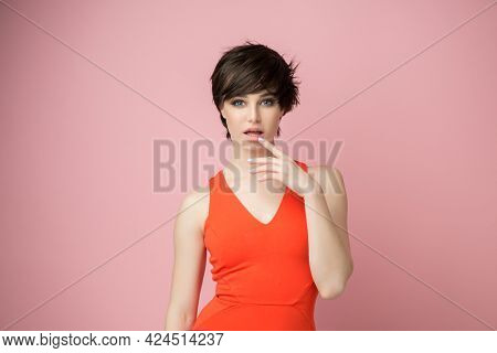 Beautiful young female posing at studio over pink background wearing vivid orange summer dress. Portrait of pretty happy brunette woman looking right at copyspace