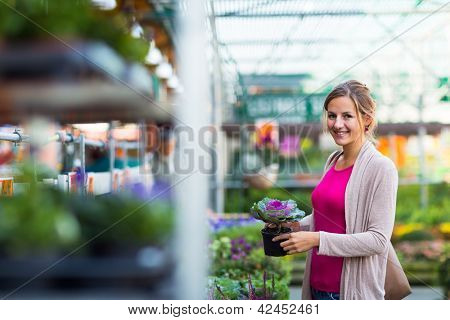 Young woman buying flowers at a garden center (color toned image; shallow DOF)