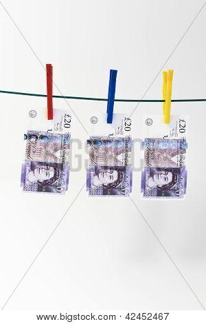 Twenty pound notes hanging with white background