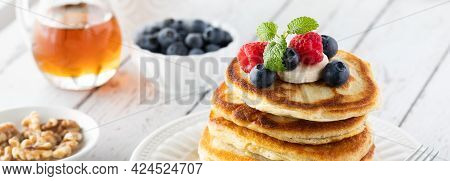 Narrow View Of A Stack Of Buttermilk Pancakes Topped With Berries And Banana Slices And Served With