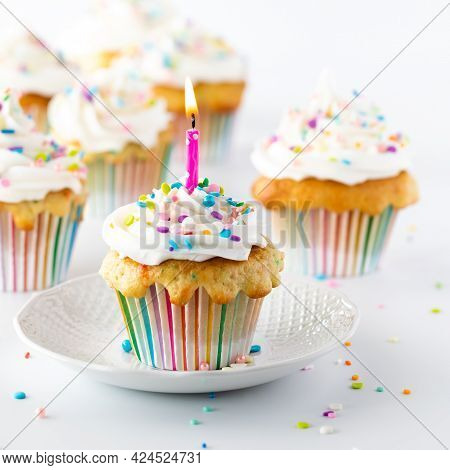 Confetti Sprinkle Cupcake With Lit A Candle And Other Cupcakes In Soft Focus In Behind. Birthday Con