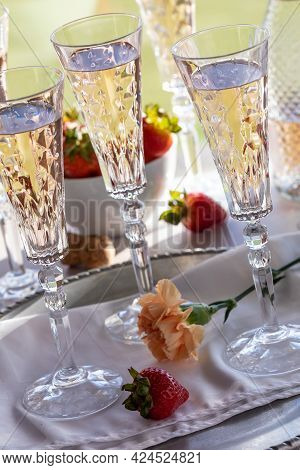 Tilted View Of Crystal Flute Glasses Filled With Rose Wine And A Bowl Of Strawberries In Behind.