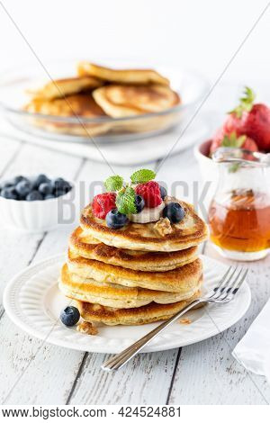 Close Up Of A Stack Of Buttermilk Pancakes, Topped With Fresh Berries And Banana Slices And Served W