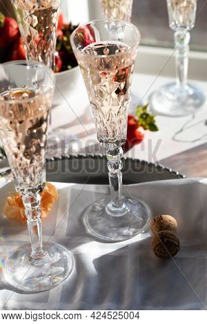 Sparkling Rose Wine In Beautiful Crystal Flute Glasses With Bright Sunshine Streaming In.
