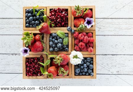 A Compartment Box Filled With Various Types Of Berries, On A Wooden Table With Copy Space On Either