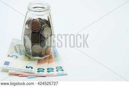 Thai Baht And Euro Coins Are Placed Together In A Glass Bottle With Euro Banknotes Placed Under The
