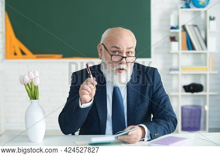 Teacher Preparing For University Exams. Professor Holding A Book And Pointing. Teacher In College On