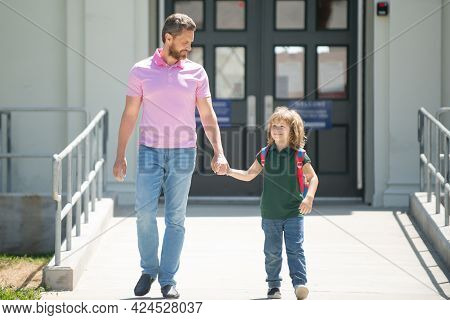 Father Walking Son To School. Parent And Pupil Of Primary School Schoolboy With Backpack. Parent Tak