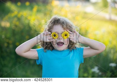 Portrait Of A Funny Child Boy Holding Flowers In Front Of Eyes . Close Up Caucasian Kids Face. Close