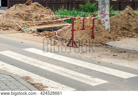 Dug Trench Behind The Crosswalk. Deep Hole Fenced With Barrier Tape And Wooden Barriers The Place Of