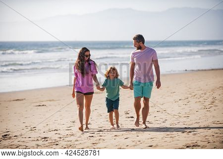 Happy Family Father, Mother And Son Child Hold Hands And Walk Along Sea Surf On Sand Beach. Active P