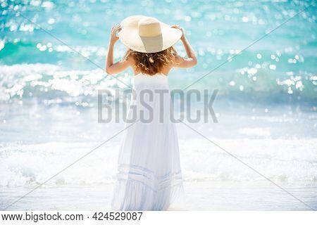 Back View Beautiful Girl With Straw Hat Enjoying Sunbath At Beach. Young Tanned Woman Enjoying Breez