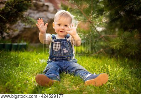 Sweet Baby Girl Playing On Green Grass In Park In Spring