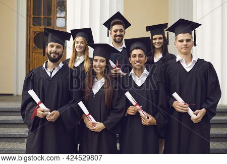 Group Of Happy Students In Mortarboards And Bachelor Gowns With Diplomas Celebrating Success.