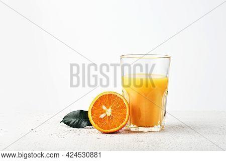 Orange Juice And A Half Of A Fresh Orange On A White Background.