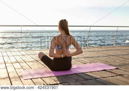Young Fit Woman Doing Hatha Yoga On The Beach In The Morning. Outdoor Meditation